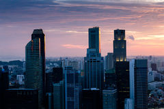 Singapore skyline sunset. Sun setting behind Singapore's skyscrapers with a violet and orange sky Royalty Free Stock Photo