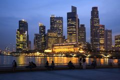 Singapore Skyline and People at Twilight. Singapore skyline at twilight. Couples and tourists sitting on the sea wall, watching the lights come on. Slight motion Royalty Free Stock Photography