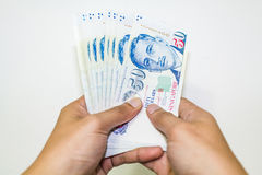 Singapore valuta med handen som isoleras i vit bakgrund Royaltyfria Foton