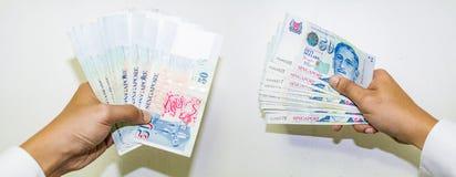 Singapore valuta med handen som isoleras i vit bakgrund, pengar Arkivbilder