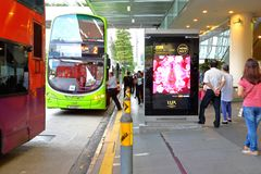 Singapore: Waiting for bus. Passenger waiting for bus at a busstop in the city Singapore Stock Images