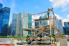 Singapore workers. SINGAPORE - MAY 09, 2013: Workers at construction site in front of Singapore downtown in Singapore. Construction industry is expected to pull Royalty Free Stock Photography