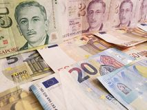 Singaporean banknotes and euro bills. Commerce, exchange, trade, trading, value, buy, sell, profit, price, rate, cash, currency, paper, money, economic stock photos