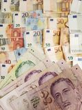 Singaporean banknotes and euro bills. Commerce, exchange, trade, trading, value, buy, sell, profit, price, rate, cash, currency, paper, money, economic royalty free stock images