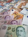 Singaporean banknotes and euro bills. Commerce, exchange, trade, trading, value, buy, sell, profit, price, rate, cash, currency, paper, money, economic stock images