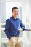 Singaporean businessman. Portrait of cheerful Singaporean businessman standing at window Stock Images