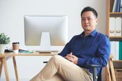 Singaporean entrepreneur. Portrait of confident Singaporean businessman sitting on chair in his office Royalty Free Stock Image