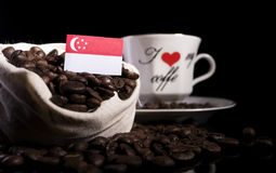Singaporean flag in a bag with coffee beans  on black Stock Photography