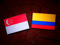 Singaporean flag with Colombian flag on a tree stump isolated Stock Photo