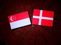 Singaporean flag with Danish flag on a tree stump isolated. Singaporean flag with Danish flag on a tree stump Stock Image