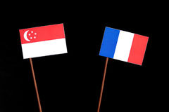 Singaporean flag with French flag on black stock photos