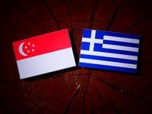 Singaporean flag with Greek flag on a tree stump isolated. Singaporean flag with Greek flag on a tree stump Stock Photo