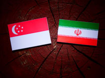 Singaporean flag with Iranian flag on a tree stump isolated. Singaporean flag with Iranian flag on a tree stump Stock Image