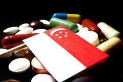 Singaporean flag with lot of medical pills isolated on black background stock image