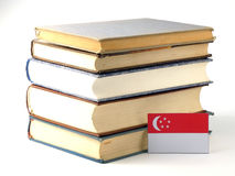 Singaporean flag with pile of books isolated on white background. Singaporean flag with pile of books isolated on white Royalty Free Stock Images