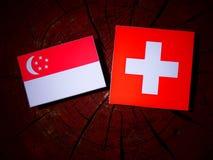 Singaporean flag with Swiss flag on a tree stump. Singaporean flag with Swiss flag on a tree stump Stock Photo