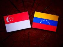 Singaporean. Flag with Venezuelan flag on a tree stump Royalty Free Stock Image