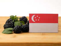 Singaporean flag on a wooden panel with blackberries isolated on royalty free stock photo