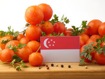 Singaporean flag on a wooden panel with tomatoes isolated on a w Stock Photos