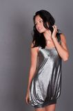 Singaporean woman. Slender young Singaporean Chinese woman in a silver dress Royalty Free Stock Images