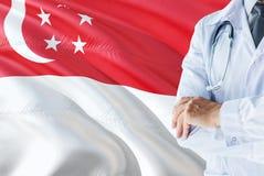 Singaporianskt doktorsanseende med stetoskopet på Singapore flaggabakgrund Nationellt v?rdsystembegrepp, medicinskt tema arkivfoton