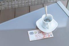 Singapour billet de dix dollars et tasse de café vide sur une table en verre de café extérieur Paiement, astuce image libre de droits