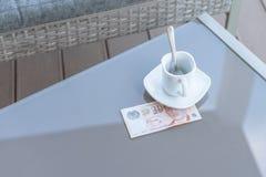 Singapour billet de dix dollars et tasse de café vide sur une table en verre de café extérieur Paiement, astuce photos stock