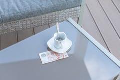 Singapour billet de dix dollars et tasse de café vide sur une table en verre de café extérieur Paiement, astuce photographie stock