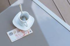 Singapour billet de dix dollars et tasse de café vide sur une table en verre de café extérieur Paiement, astuce photo libre de droits