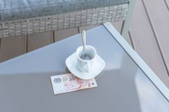 Singapour billet de dix dollars et tasse de café vide sur une table en verre de café extérieur Paiement, astuce photographie stock libre de droits