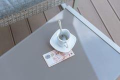 Singapour billet de dix dollars et tasse de café vide sur une table en verre de café extérieur Paiement, astuce photo stock