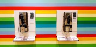 Singapur, Singapur Czerwiec 27, 2018: Dwa jawny telefon na tęcza koloru tle przy Changi lotniskiem, Singapur Obrazy Stock