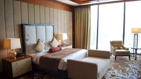 SINGAPUR - 2 de abril de 2015: Dormitorio principal hermoso con la visión en una habitación de lujo de Marina Bay Sands Resort fotografía de archivo