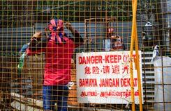 Singapur 2 DE ABRIL DE 2019: trabajador que lleva el funcionamiento de la bufanda de AC Milan en emplazamiento de la obra fotografía de archivo