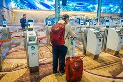 SINGAPUR, SINGAPUR - 30 DE ENERO DE 2018: Mujer no identificada que hace a uno mismo - regístrese el quiosco en el aeropuerto de  imagen de archivo libre de regalías
