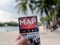 SINGAPUR - 23 de noviembre de 2018: Hombre que celebra un mapa de Singapur en la isla del sentosa foto de archivo