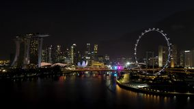 Singapur - 25 de septiembre de 2018: Vista aérea de la ciudad grande con muchas luces, cielo nublado, y noria en la noche tiro imágenes de archivo libres de regalías
