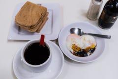 Singapur-Frühstück Kaya Toast mit Kokosnuss-Marmelade und schwarzem Kaffee Lizenzfreies Stockfoto
