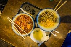 SINGAPUR SINGAPUR, LUTY, - 01, 2018: Nad widok trzy talerza z jedzeniem, kluskami, kurczakiem i polewką nad drewnianym, Zdjęcie Royalty Free