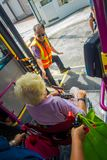 SINGAPUR SINGAPUR, LUTY, - 01, 2018: Niezidentyfikowana stara kobieta w koła krześle opuszcza autobusu i kierowcy autobusu dawać Fotografia Stock