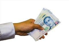 Singapur-Währung mit der Hand lokalisiert im weißen Hintergrund Lizenzfreie Stockfotos