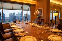 SINGAPURA - 23 de julho de 2016: sala de hotel de luxo com interior moderno, mesa de jantar e uma opinião impressionante Marina B Imagem de Stock Royalty Free