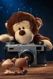 Singe de peluche avec un vieil appareil-photo de film photographiant des animaux de jouet Photographie stock libre de droits