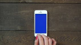 Singe Tap Hand Smartphone with Blue Screen. Female Hand Using Vertical Smartphone with Blue Screen Singe Tap on the Background of Wooden Table stock video footage