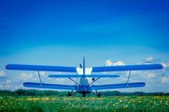 Singel-motor ljust flygplan på flygfältet som är vitt med blåa vingar, i fältet på det gröna gräset mot den blåa himlen arkivbild
