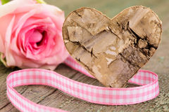 Singel rose as present with carved wooden heart Royalty Free Stock Images