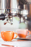 Singel som skjutas i orange kopp kaffe Arkivfoton