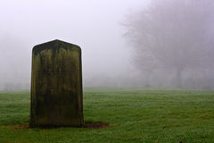 Singelgravestone i en spöklik kyrkogård Arkivbilder