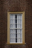 Singelguling inramade fönstret på väggen för röd tegelsten. Arkivbild