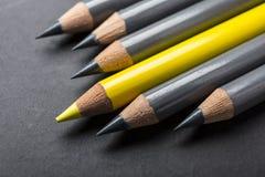 Singelgulingblyertspenna i rad av färgblyertspennor Arkivfoto